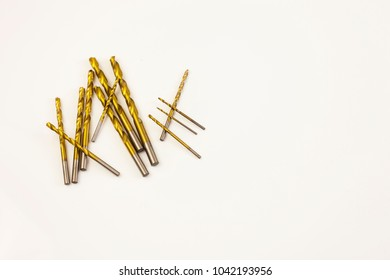 Several brass wood drill bits on white surface