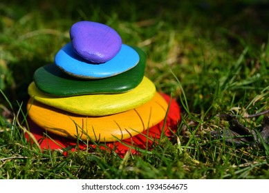Several brightly colored pebbles painted in rainbow colors lie on top of one another in a meadow with green grass - Shutterstock ID 1934564675