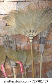 Several broomsticks are set against the wall