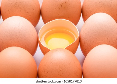 Several brown organic eggs and one broken egg with visible egg yolk.