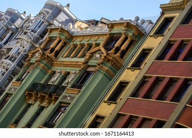 Several buildings facade with several coours, several windows and sunlight.