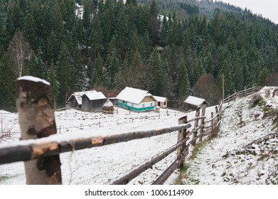 several buildings in the form of tree houses are on a mountain plain covered with snow around them a fence