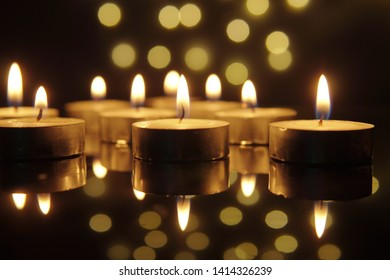 Several burning light candle fire with black background. Depth of field effect.