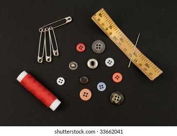 Several buttons, thread, needle and other objects to sew on a black background