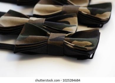 Several camouflage butterfly-neckties of protective color on a white background. An original accessory for completing the style. a combination of incongruous: war and fashion
