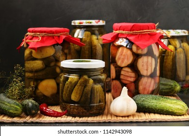 Several cans of cucumbers are located on a table on a dark background, Different kinds of marinated cucumbers for the winter