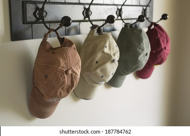 Several caps hang on hooks near a door. Focus on worn cap in foreground.