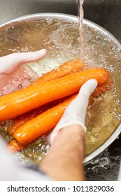 Several carrots washing under running water. Washing carrots in water with bubbles in metal bowl.