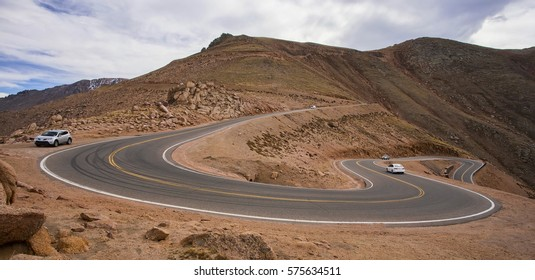 Several cars climbing the long, steep, winding road to the top of Pikes Peak in Colorado.