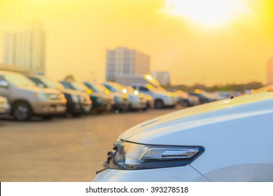 Several cars parked in a parking lot against sun rise