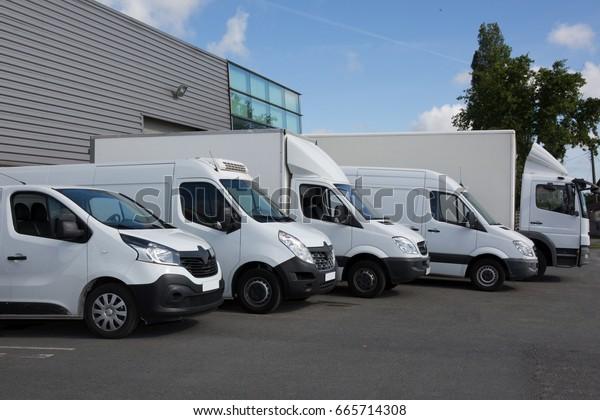 Mehrere Autos und Lastkraftwagen parken auf Parkplatz zum Verkauf