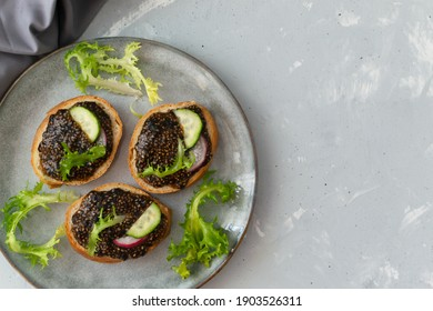 Several chia seed sandwich on pieces of baguette with vegetables and herbs on a gray plate on a gray background. Copy space. Top view. Horizontal orientation.