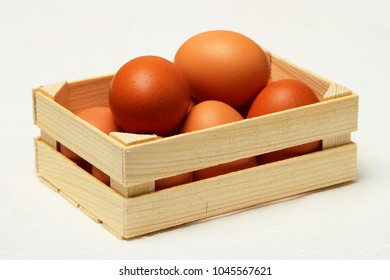 Several chicken eggs in wooden box on white background.