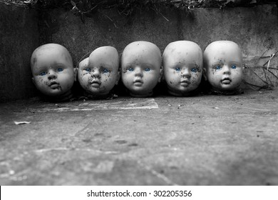 several children head doll with blue eyes lie in the old yard - scary stories - fear - a fairy tale