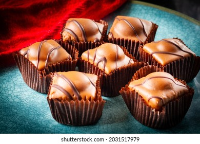 Several chocolate fondant fancies cakes with icing on a turquoise plate with a red cloth