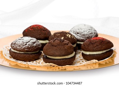 Several chocolate whoopie pies with cream cheese filling on a gold plate.