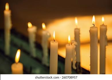 Several church candles against a dark background
