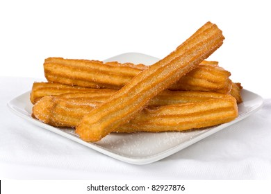 Several churros on small plate against white background.