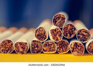 Several cigarettes lie on a yellow background and a black background. Toned. Close up.