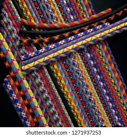 Several climbing ropes in aligned compilation against black background. Colorful pattern