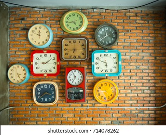 Several clocks on a brick wall showing different times.