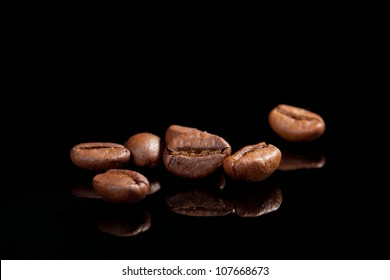 Several coffee beans isolated on black background with reflection. Culinary coffee background.