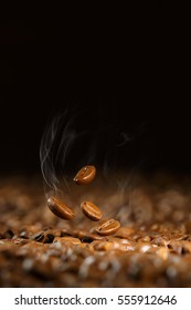 several coffee beans thrown up on a black background