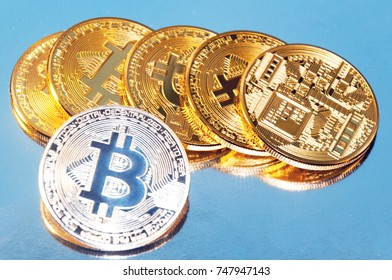 Several coins of bitcoins. Bright glow, toning and blurring. The concept of crypto currency