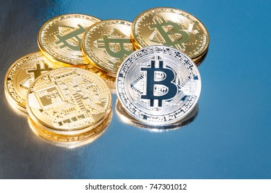 Several coins of bitcoins lie on the keyboard. Bright glow, toning and blurring. The concept of crypto currency