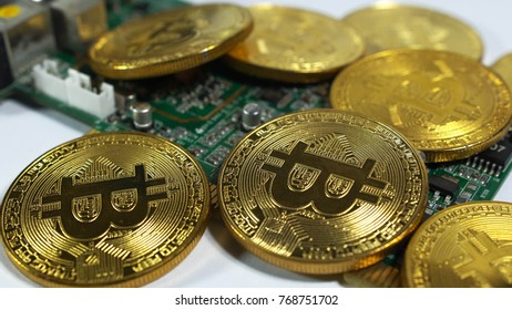 several coins of bitcoins and a strip of electronic memory on a light background.