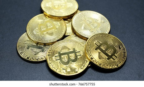 several coins of gold bitcoins on a dark background.