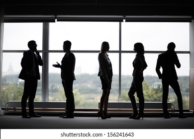 Several colleagues communicating at meeting against window