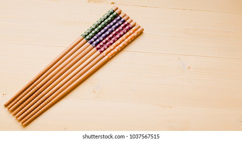 Several colorful chop sticks on yellow table surface laid out at angle