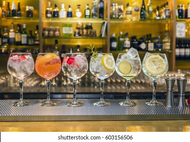 Several colorful cocktails in large wine glasses in a row in a classic bar environment with dozens of blurry liquor bottles in the background.