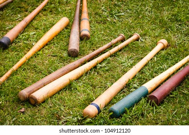 Several colorful old wooden vintage baseball bats are scattered on a green grass background