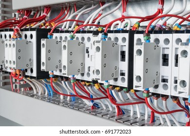 Several contactors arranged in a row in an electrical closet. The contactors connected wire number coded. Contactors with front auxiliary contacts. The wires go into perforated cable channels.