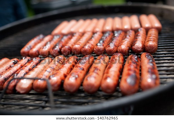 Several cooking hot dogs on a grill