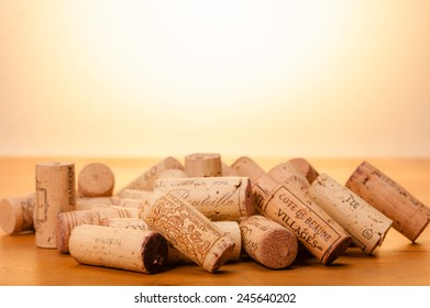 """Several Corks on wood. """" Mis en Bouteille"""" (""""filled in the bottle or bottled"""") or the Origin of the Wine and or the Vintage is printed on them. Background is kept in warm light to represent the sun."""