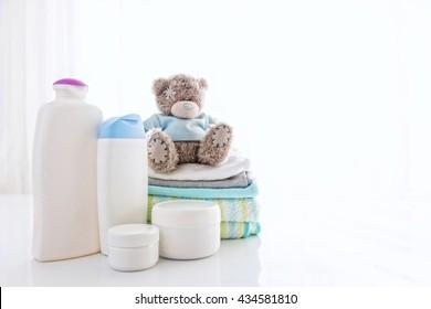 Mehrere Kosmetikprodukte für Kinder neben Handtüchern und Teddybären.