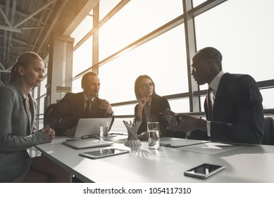 Several co-workers sitting at table in light room with large windows, they are attentively listening to african businessman speaking to them