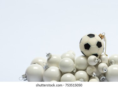 Several creamy white and one soccer shaped Christmas tree baubles against a white background (landscape orientation)