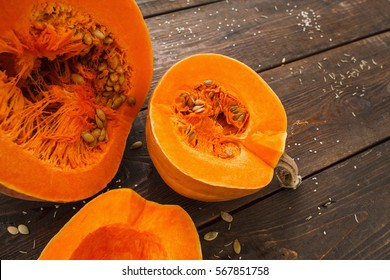Several cut pumpkins on wood closeup. Fresh orange squashes on wooden table, country autumn background. Seasonal, harvest, fall concept