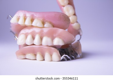 Several dentures stacked on white background.