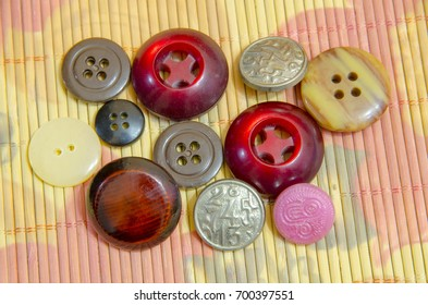 Several different buttons lie on a bamboo mat.