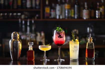 several different cocktails, shaker and bitters on the bar