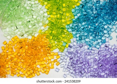 several different dyed polymer granulates in laboratory on table