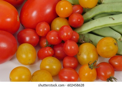 Several different fresh organic tomatoes on white table