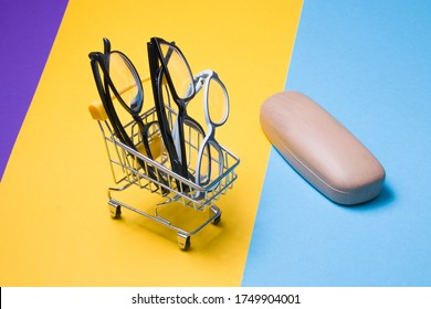 several different glasses in a small shopping trolley on a colorful background, a case for glasses on the background,eyewear store for adults and children
