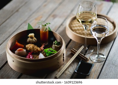 Several different traditional Chinese dimsum dumplings in a wooden basket cooked for guests on a wooden table in a restaurant. Asian food.