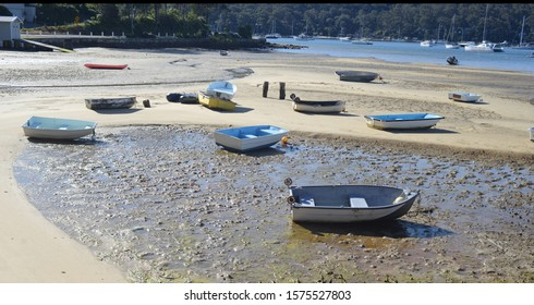 Several dinghies resting on sand at low tide Australia